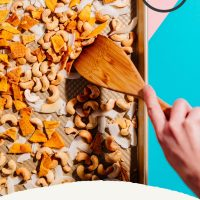 Using a wooden spatula to stir a batch of homemade Trail Mix made with mango, coconut, and cashews