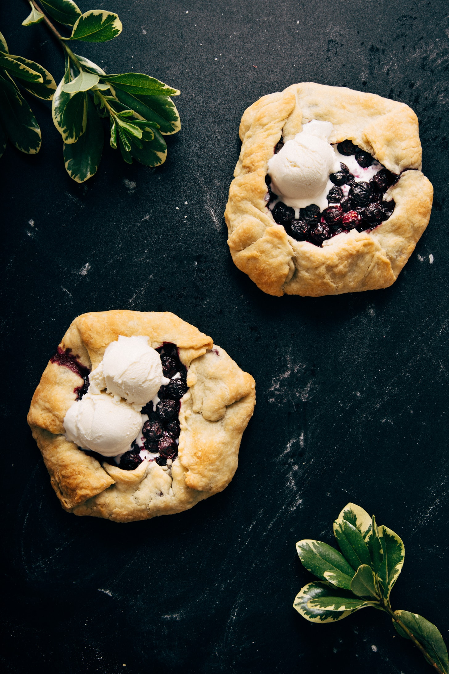 Two vegan Mini Blueberry Galettes topped with scoops of ice cream