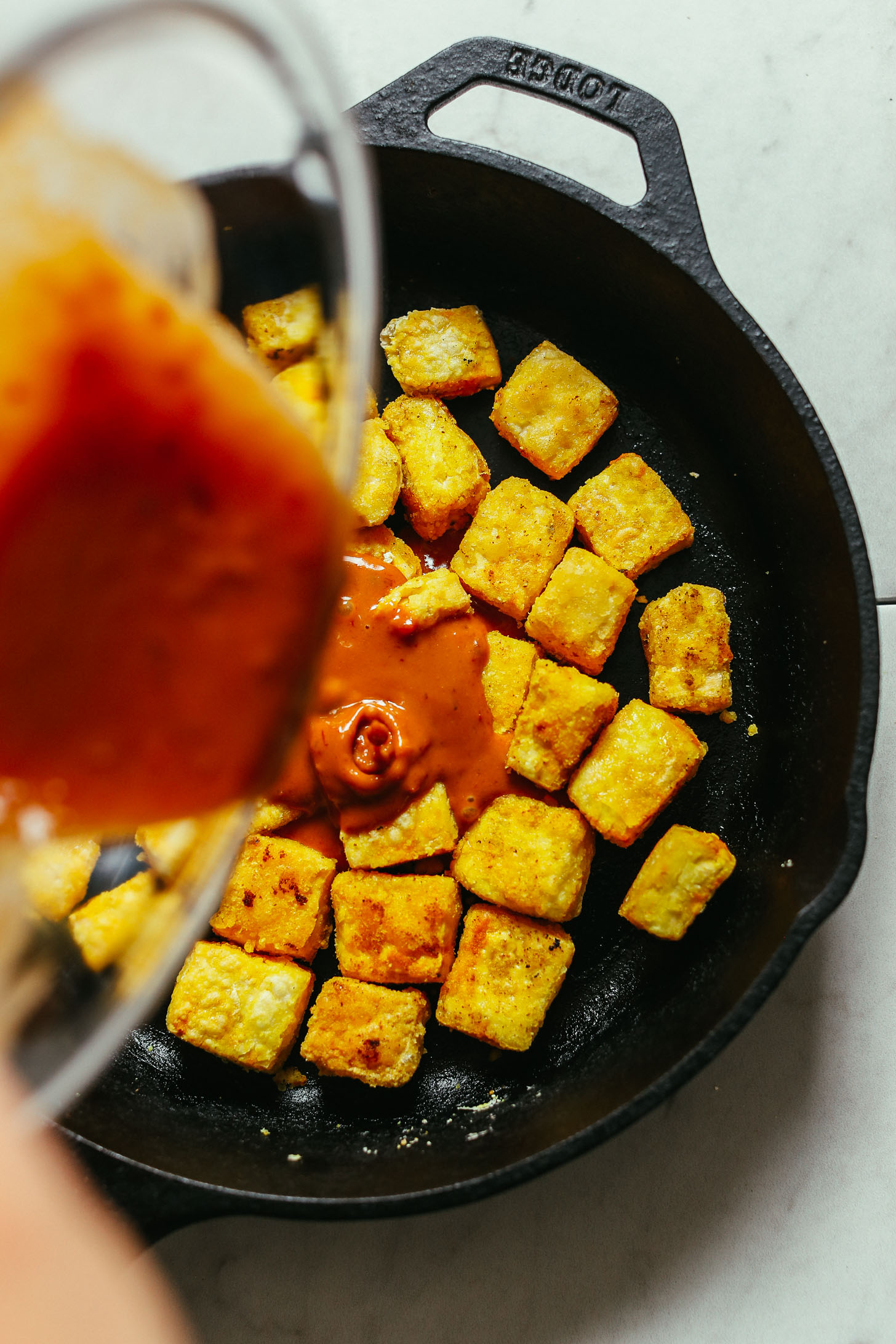 Pouring sauce into a skillet of cubed tofu