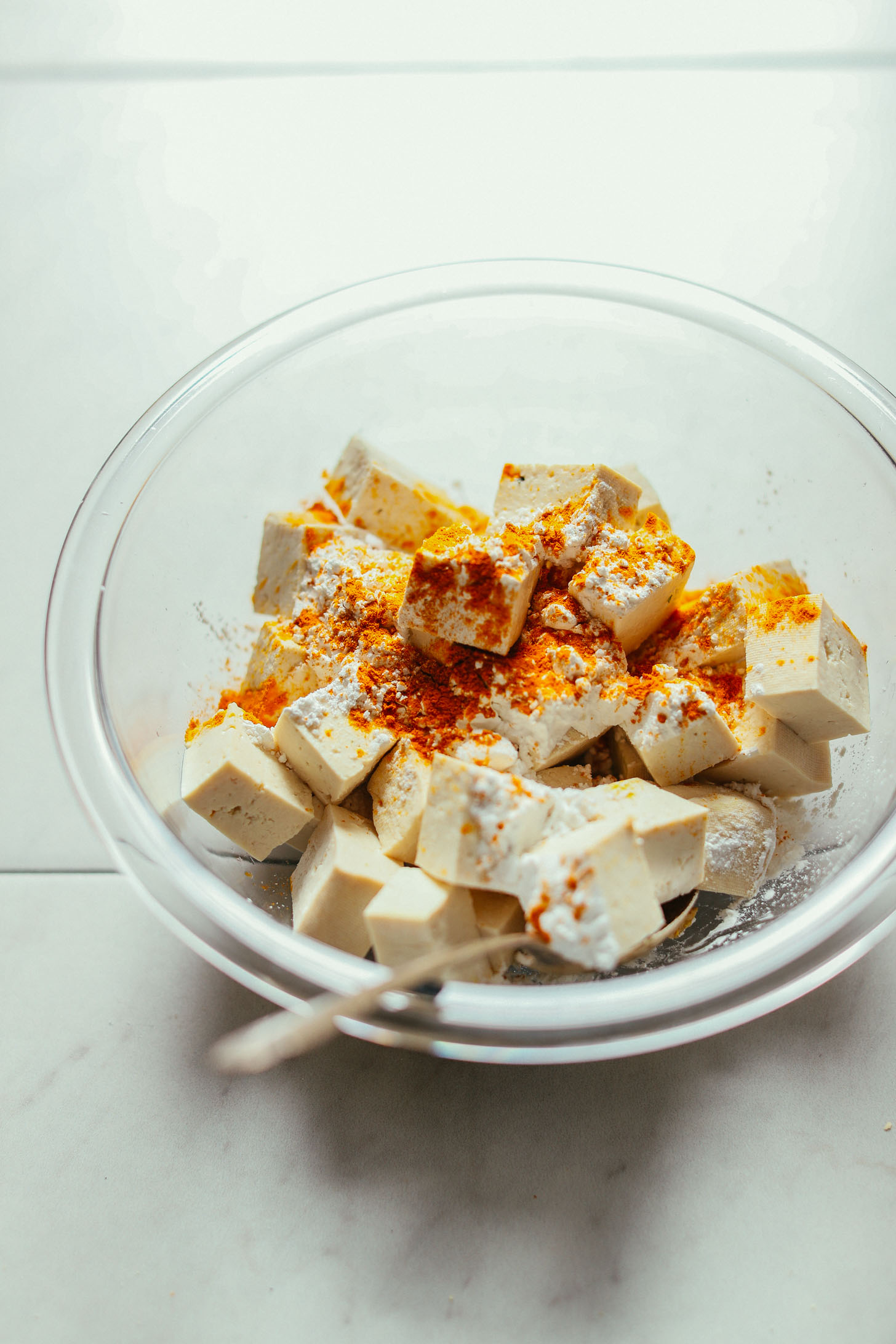 Cubed tofu seasoned with curry powder and cornstarch, tossed with a metal spoon in a glass bowl