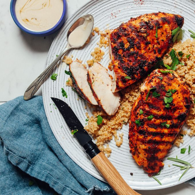 Plate of Marinated Grilled Chicken beside quinoa and a bowl of tahini sauce