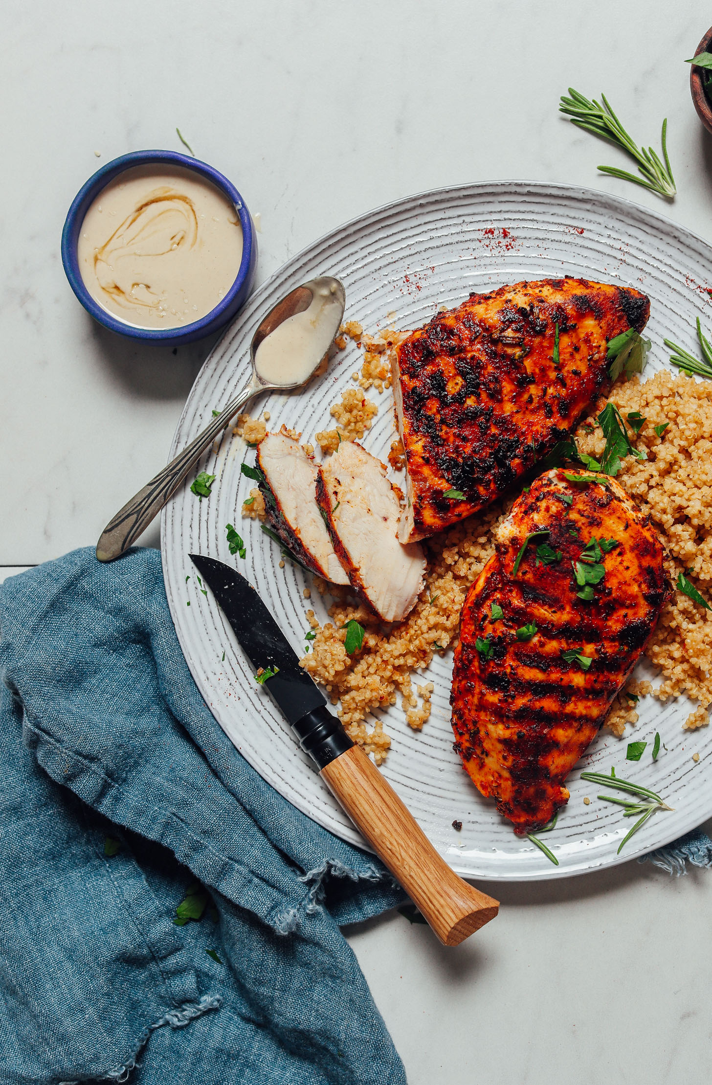 Bowl of tahini sauce beside a plate of Marinated Grilled Chicken Breasts served over quinoa