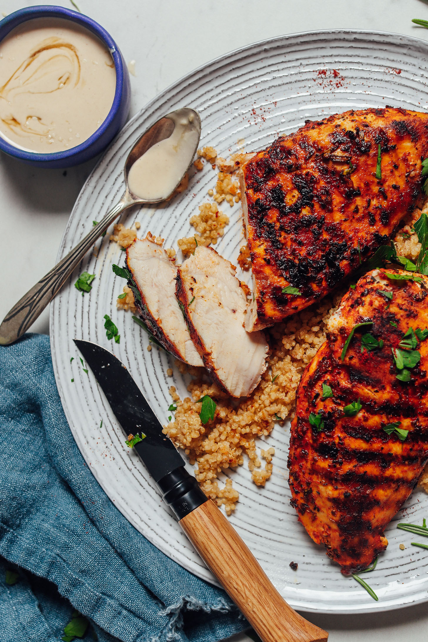 Marinated Grilled Chicken Breasts on a plate with chicken and tahini sauce for serving