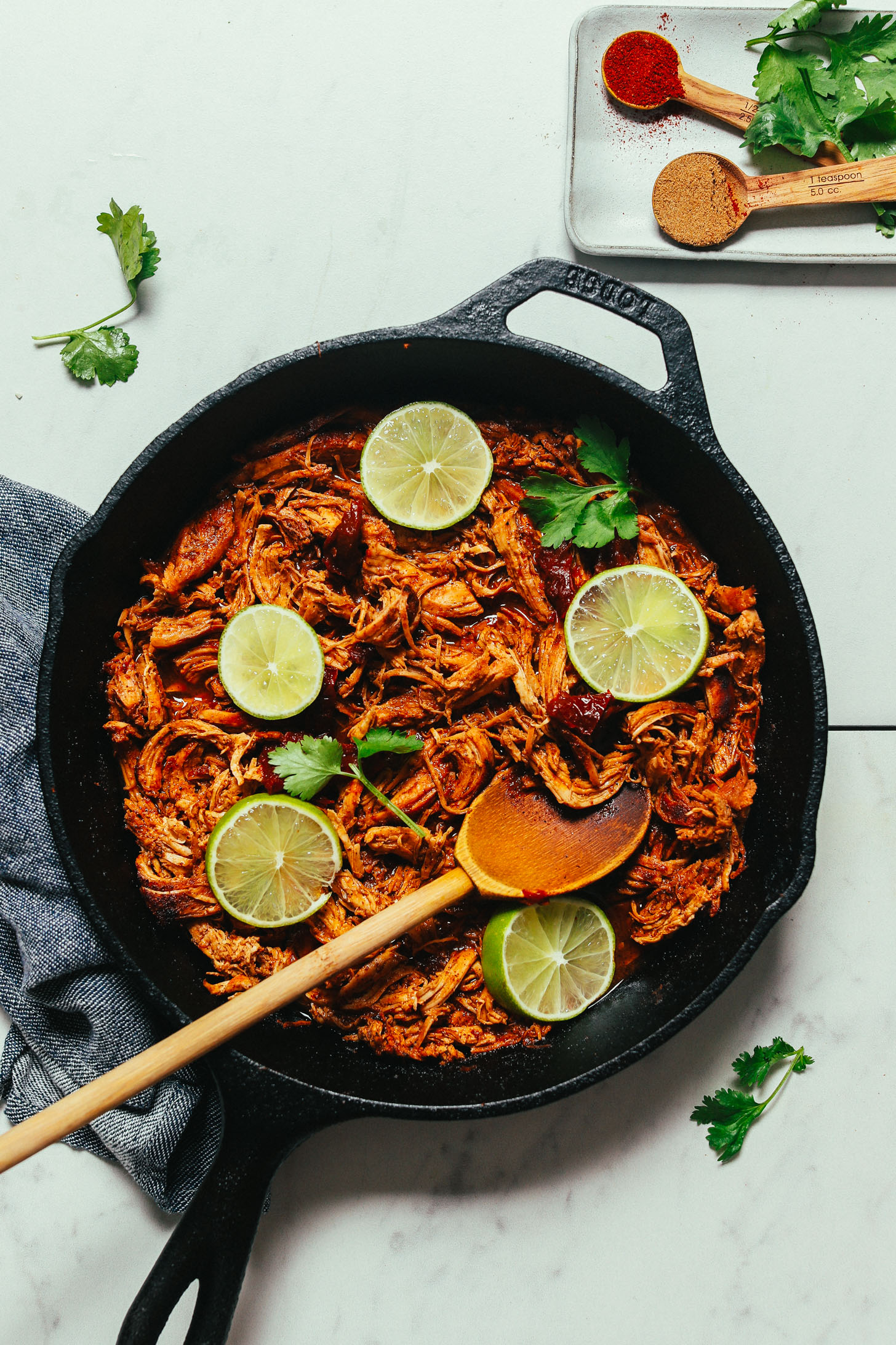 Wooden spoon in a skillet of Mexican Shredded Chicken made with chipotle peppers and lime
