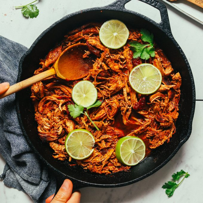 Large cast iron skillet filled with a batch of our Mexican Shredded Chicken recipe