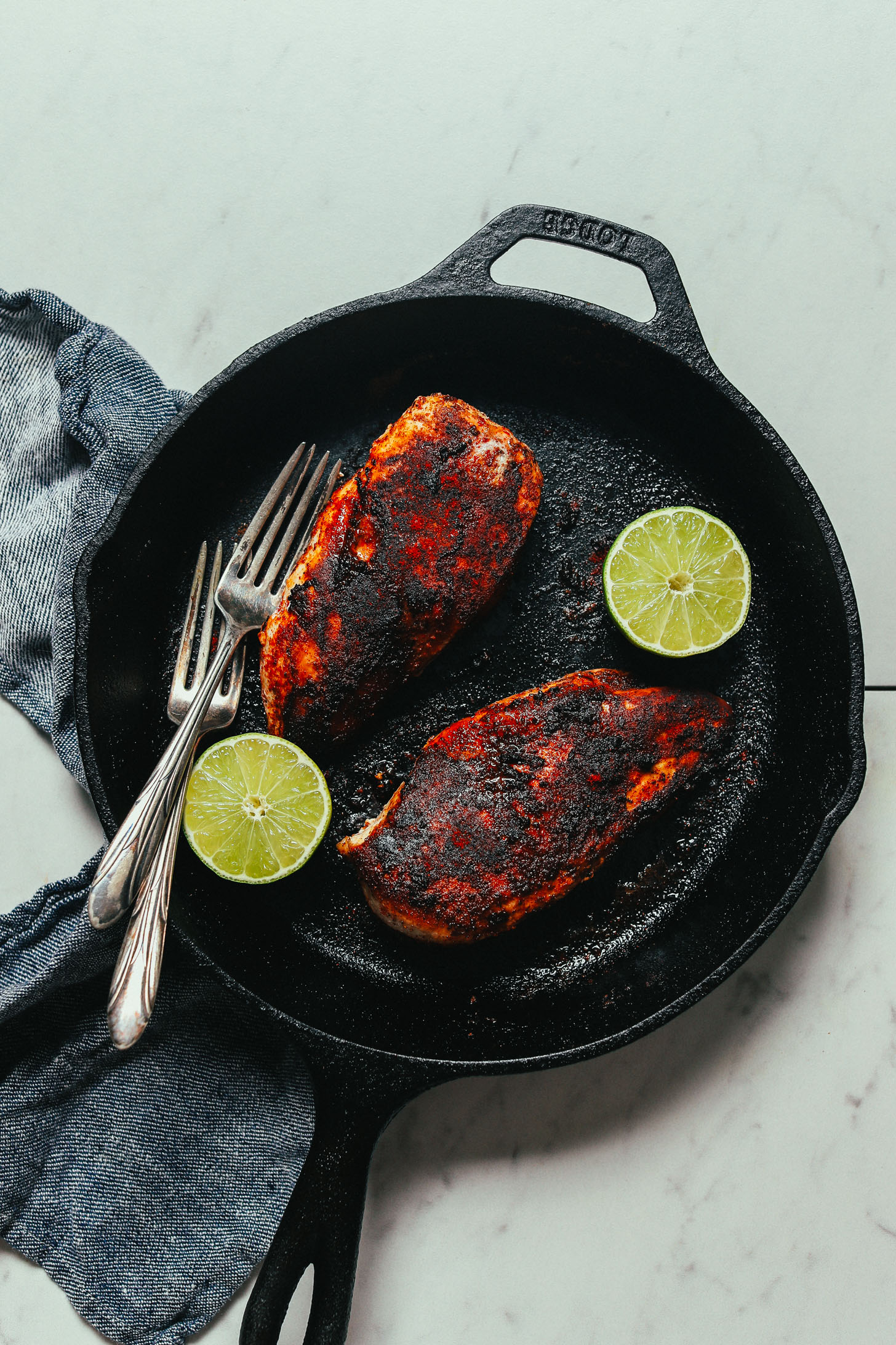 Skillet of cooked Mexican-seasoned boneless skinless chicken breasts and limes