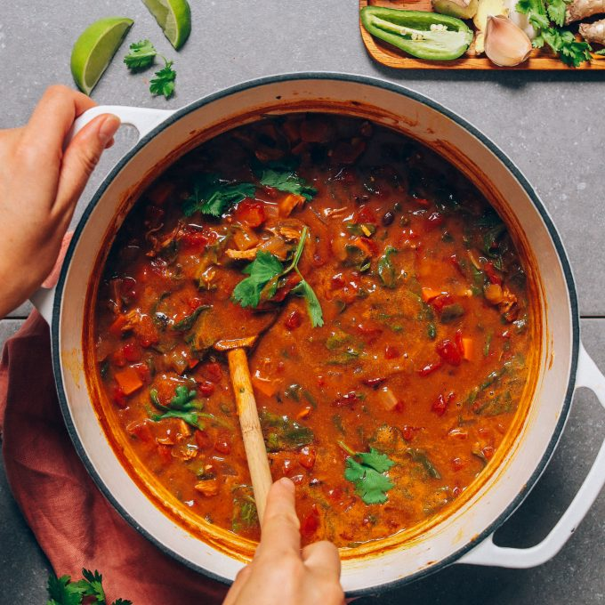 Stirring a pot of our delicious Pumpkin Black Bean Soup made with Thai and chili flavors
