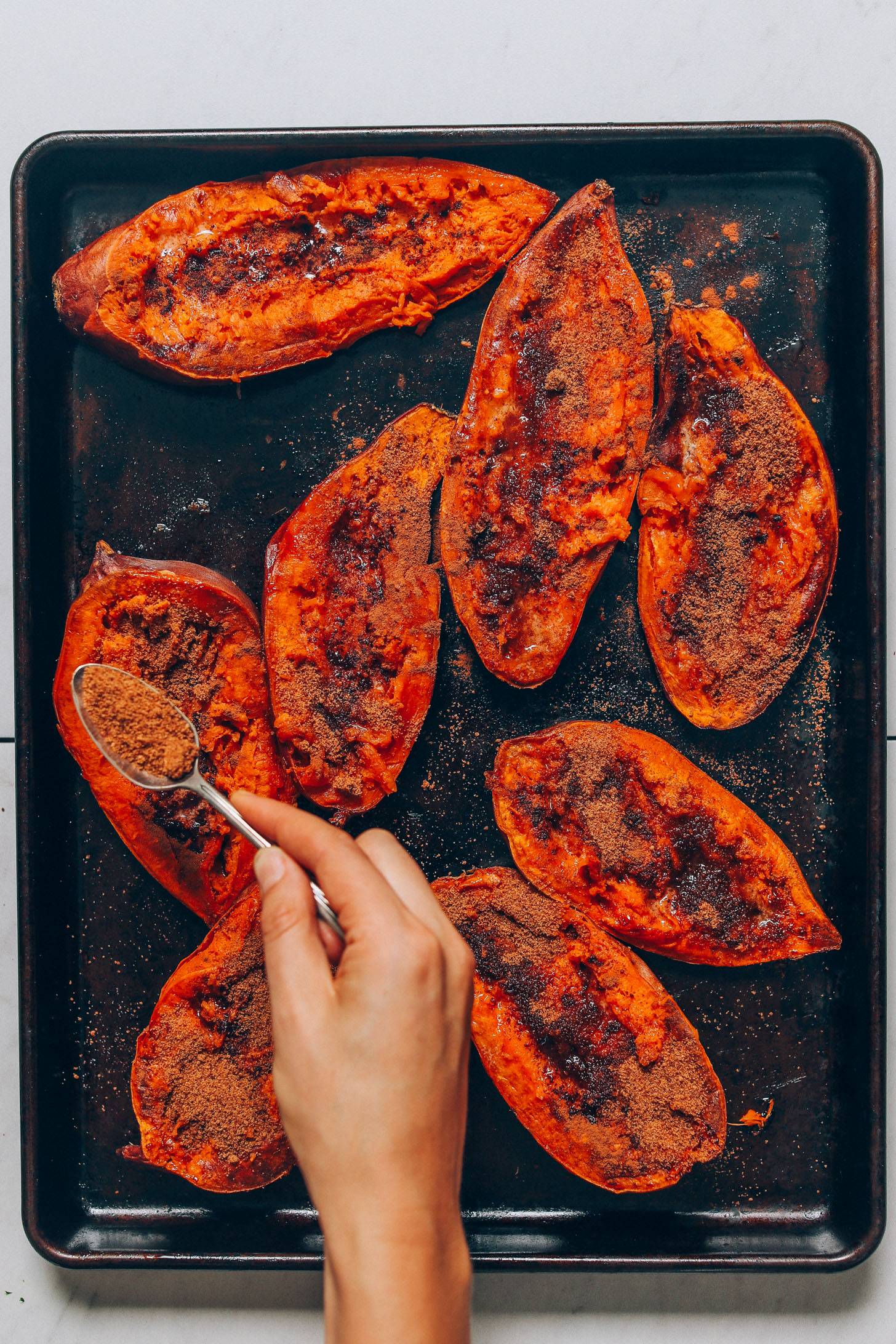 Sprinkling coconut sugar on halved, baked sweet potatoes to make Sweet Potato Casserole Boats