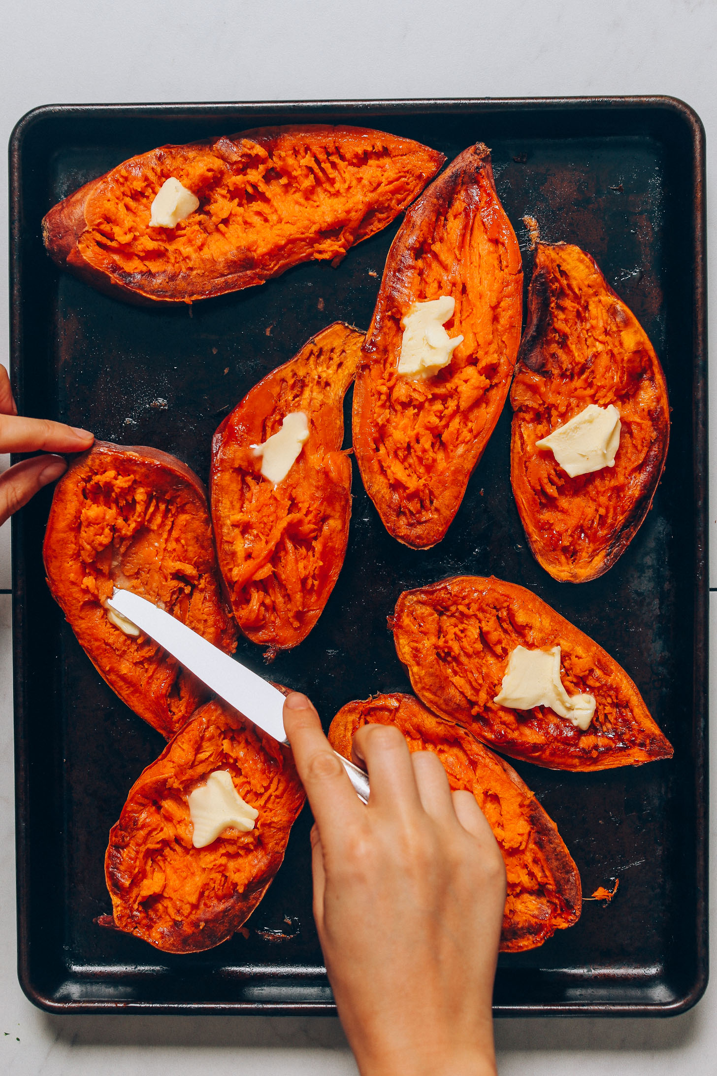 Using a knife to spread vegan butter onto halved Sweet Potato Boats