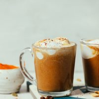 Mugs of our easy DIY Pumpkin Spice Latte topped with coconut whipped cream and pumpkin pie spice
