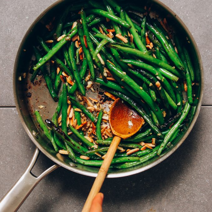 Using a wooden spoon to stir a pot of Garlic Green Beans for a Thanksgiving side