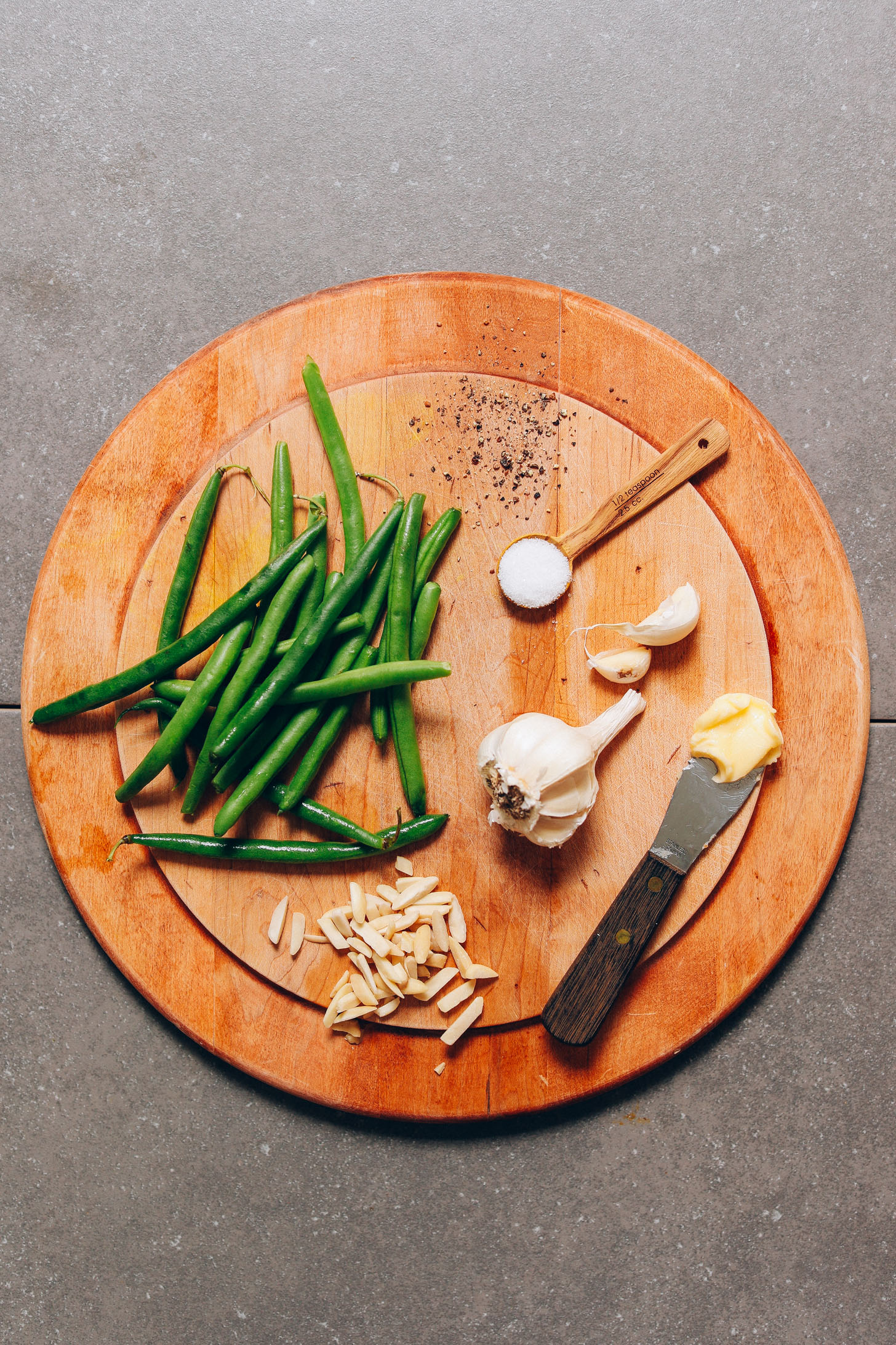 Wood cutting board with ingredients for making our easy Green Beans recipe