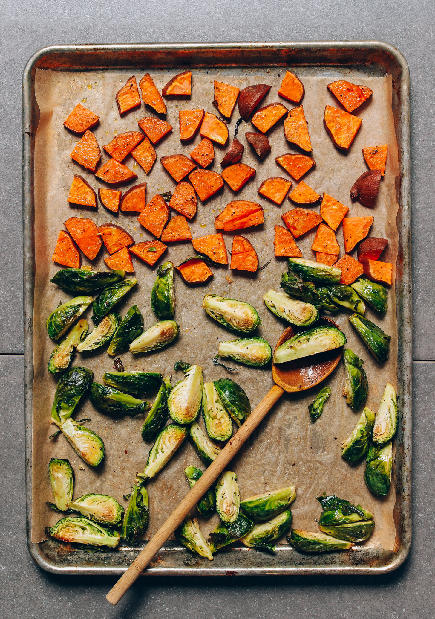 Parchment-lined baking sheet of roasted sweet potatoes and Brussels sprouts for our Fall Breakfast Hash recipe