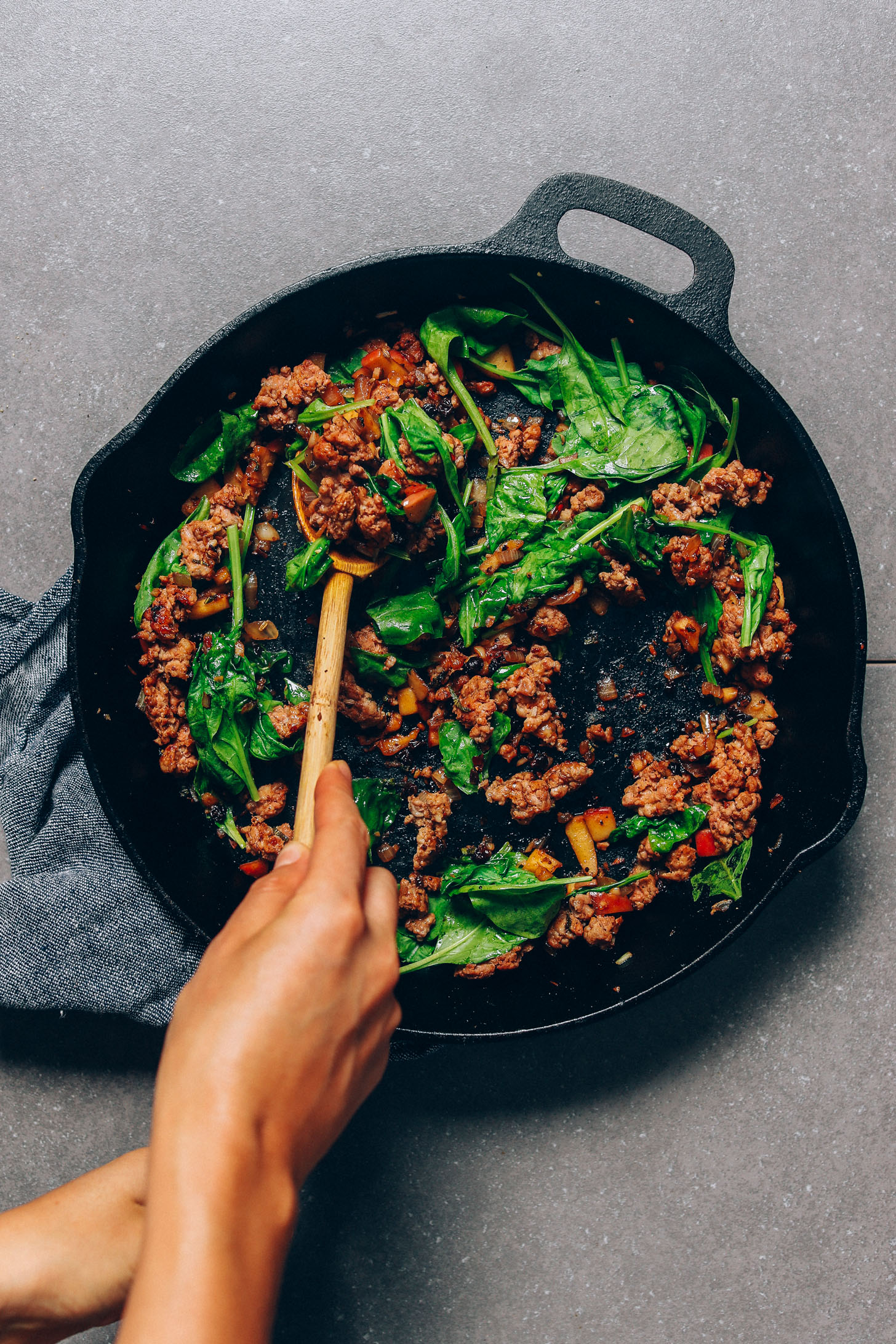 Sautéing spinach and sausage in a large skillet for our Fall Sweet Potato Breakfast Hash recipe