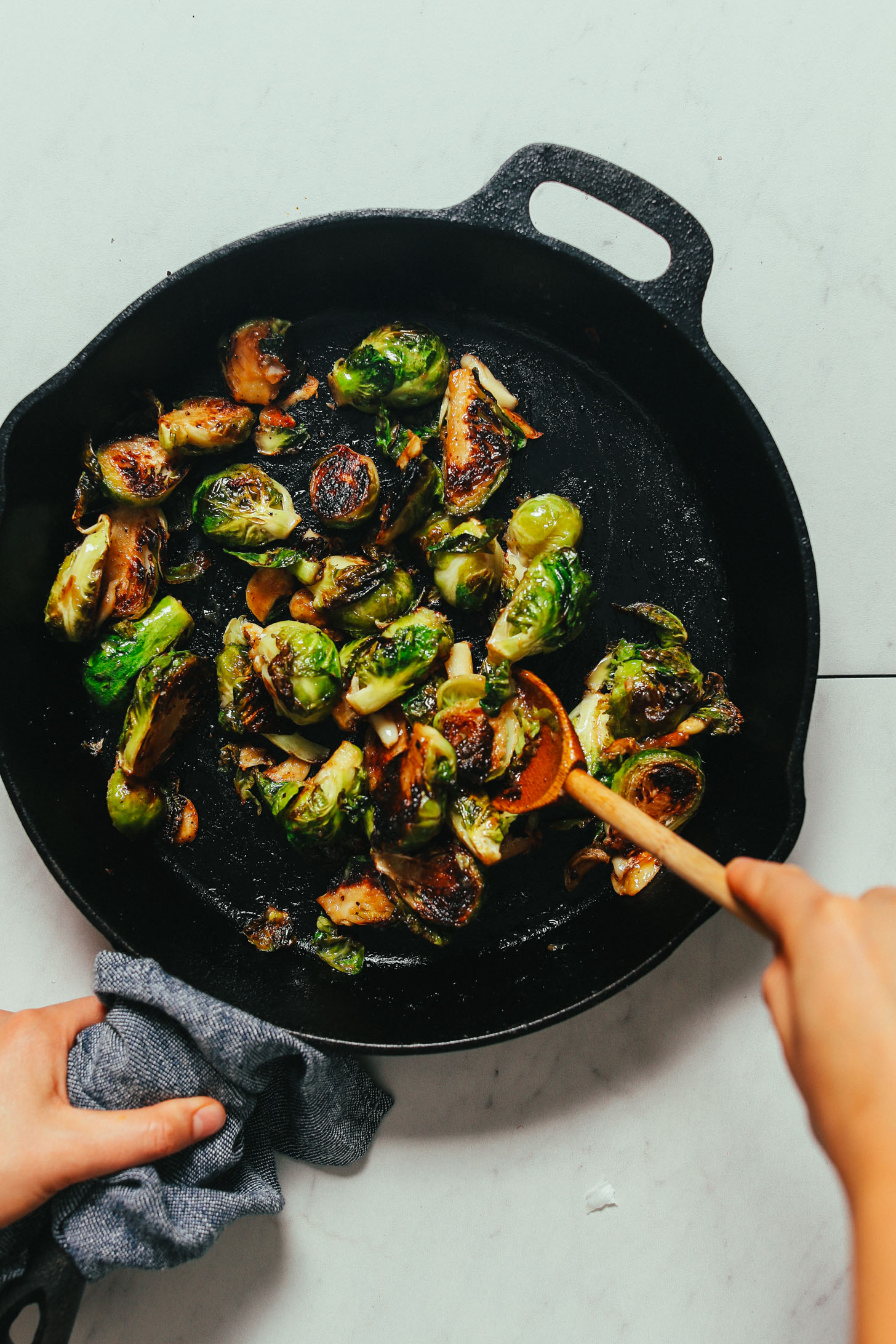 Stirring a pan of crispy Roasted Brussels Sprouts made with a miso glaze