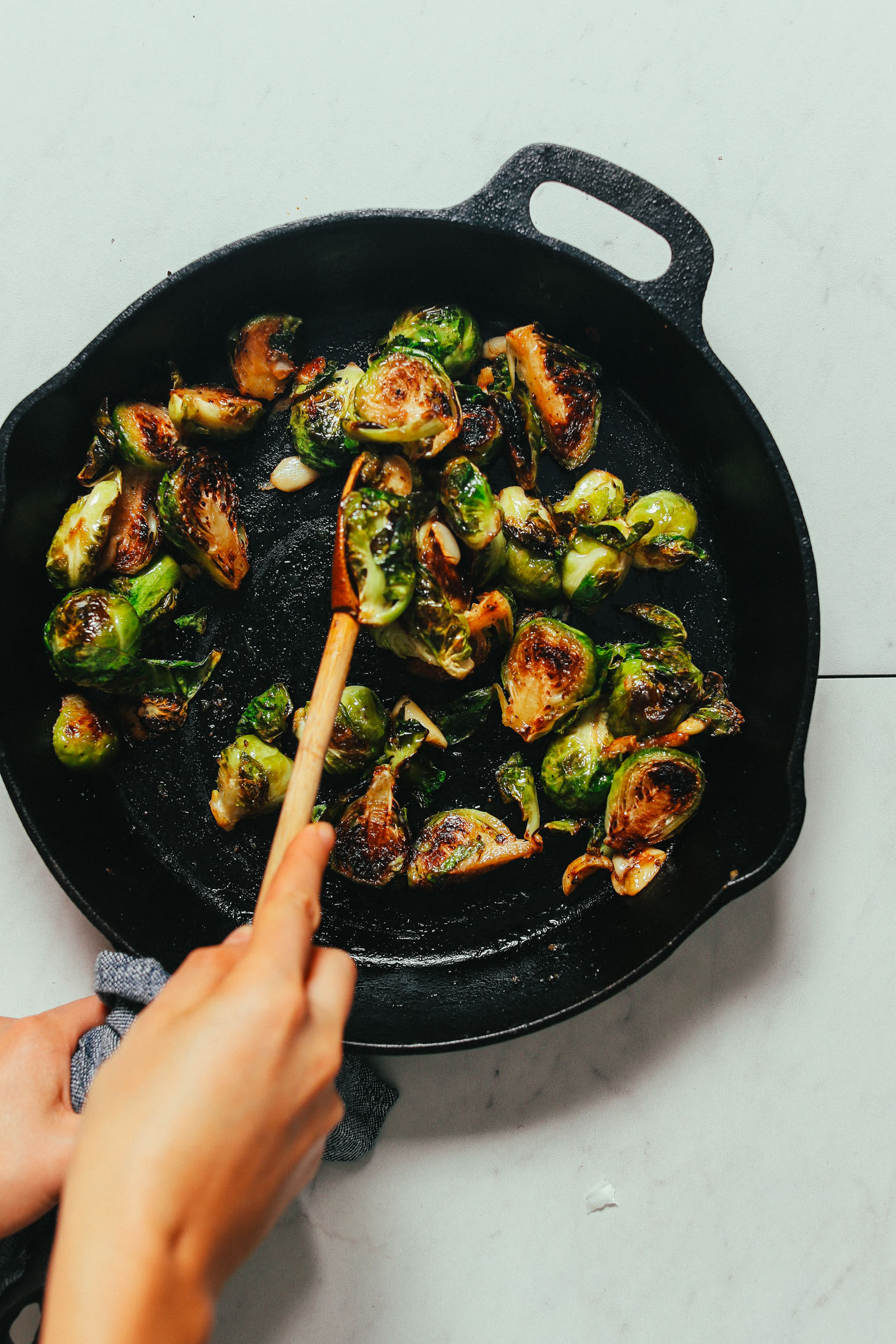 Using a wooden spoon to coat Roasted Brussels Sprouts with Miso Glaze for a delicious Thanksgiving side