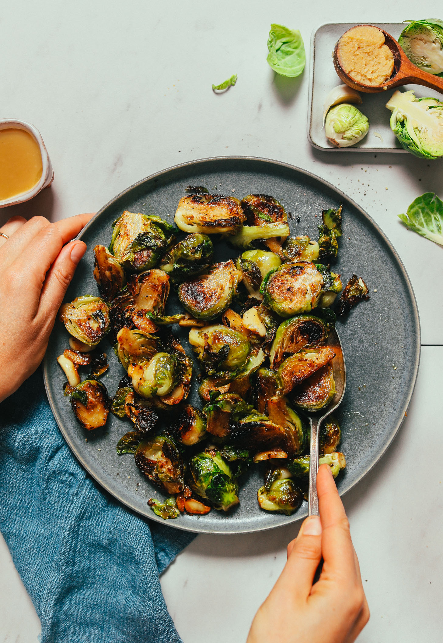 Plate of Miso-Glazed Roasted Brussels Sprouts beside ingredients used to make them