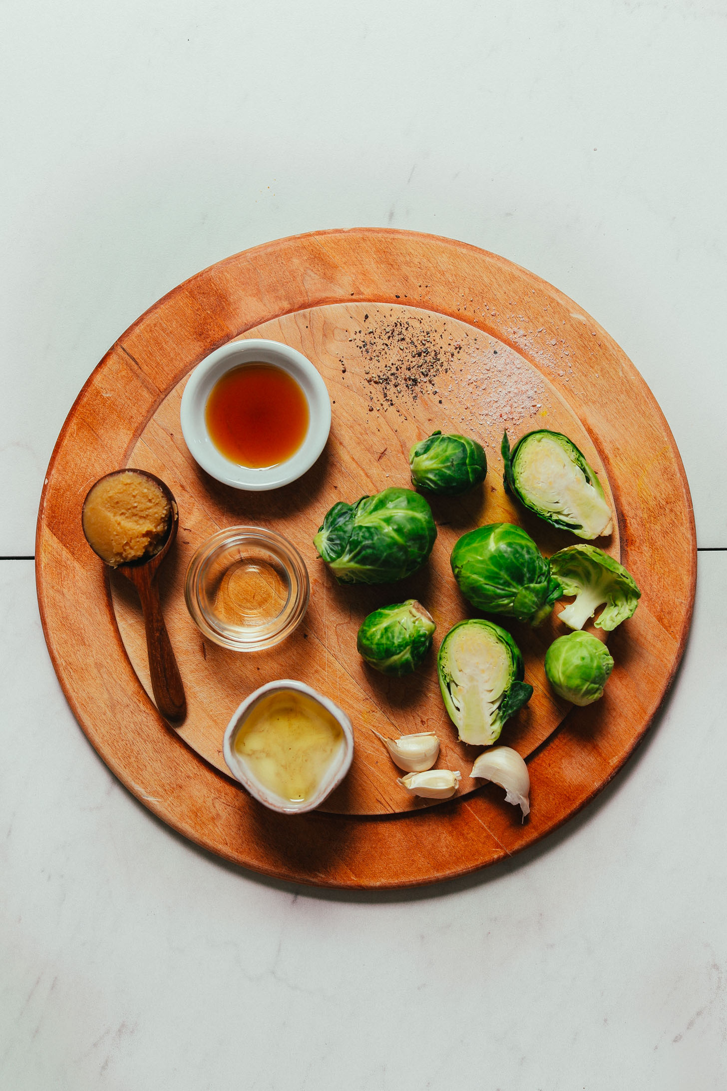 Wood cutting board with ingredients for making our easy Roasted Brussels Sprouts recipe