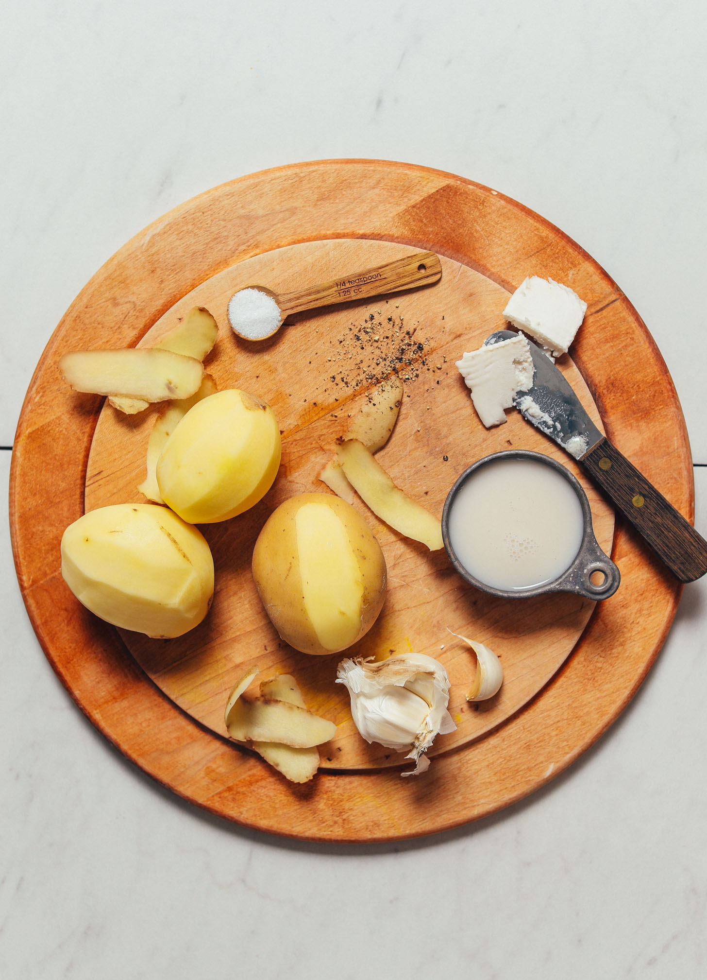 Wood cutting board with ingredients for making our vegan Mashed Potatoes recipe
