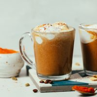 Mug of our dairy-free Pumpkin Spice Latte recipe topped with coconut whipped cream