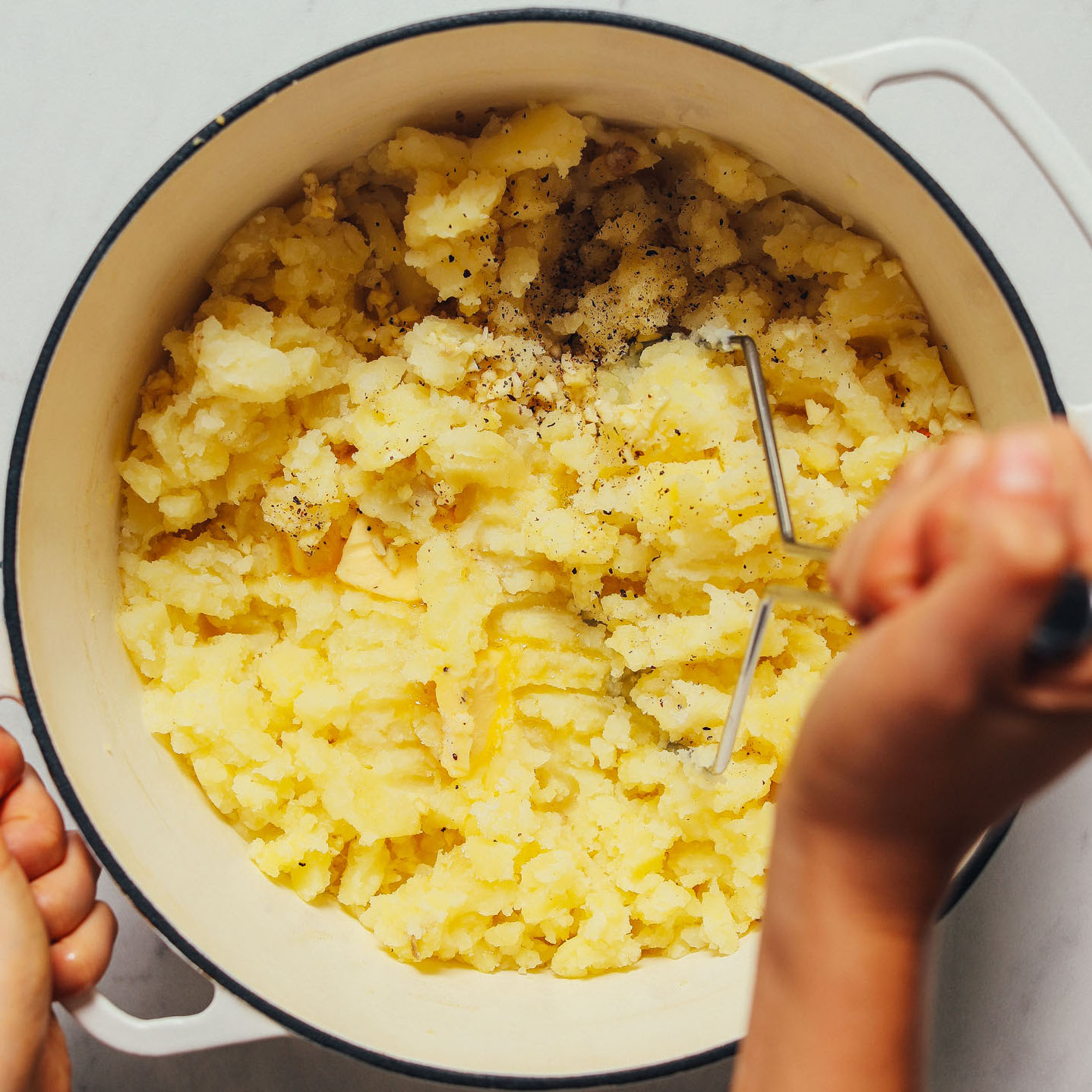 Using a potato masher to show How to Make Mashed Potatoes