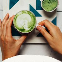 Holding a mug of our Moringa Latte recipe for a comforting and healthy morning beverage