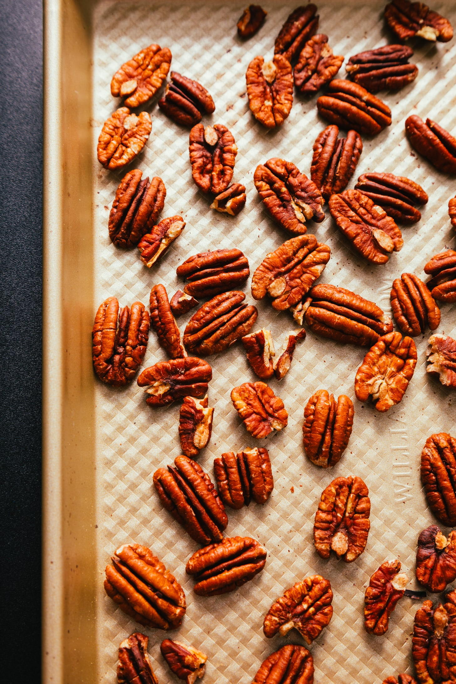 Toasting pecans on a baking sheet to make our Turtle Candies recipe
