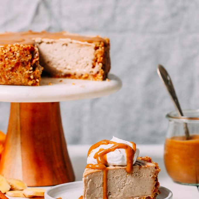 Slice of vegan cheesecake made with chai spices resting beside the rest of the cheesecake