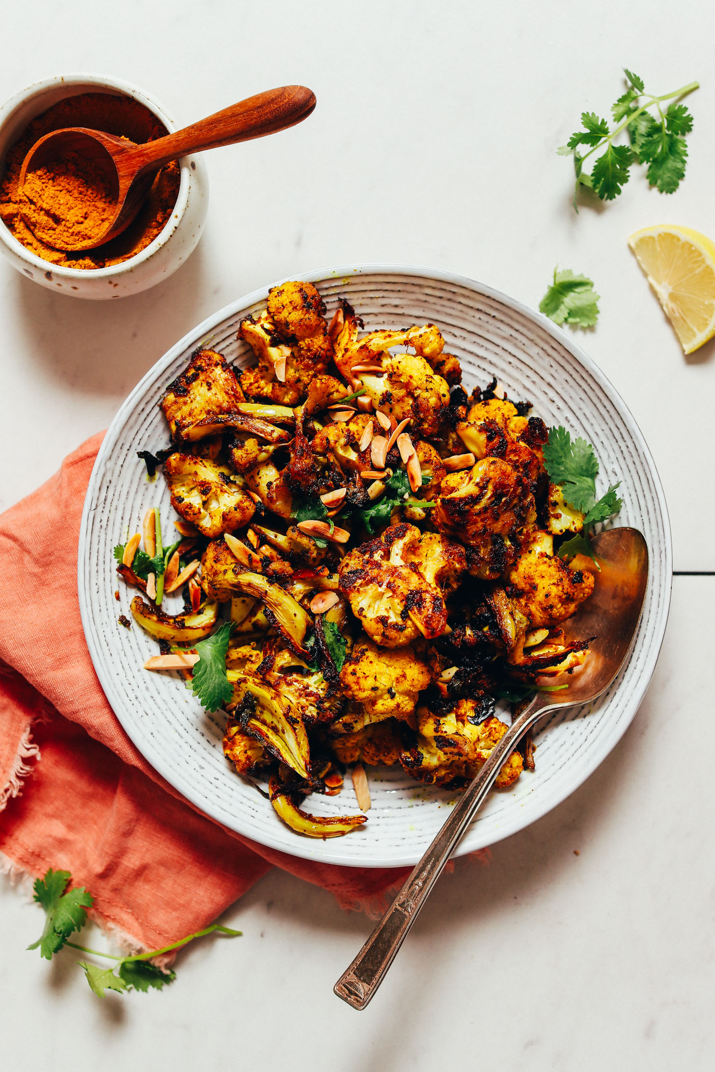 Bowl of Quick Crispy Cauliflower topped with toasted almonds and fresh cilantro beside a dish of curry powder