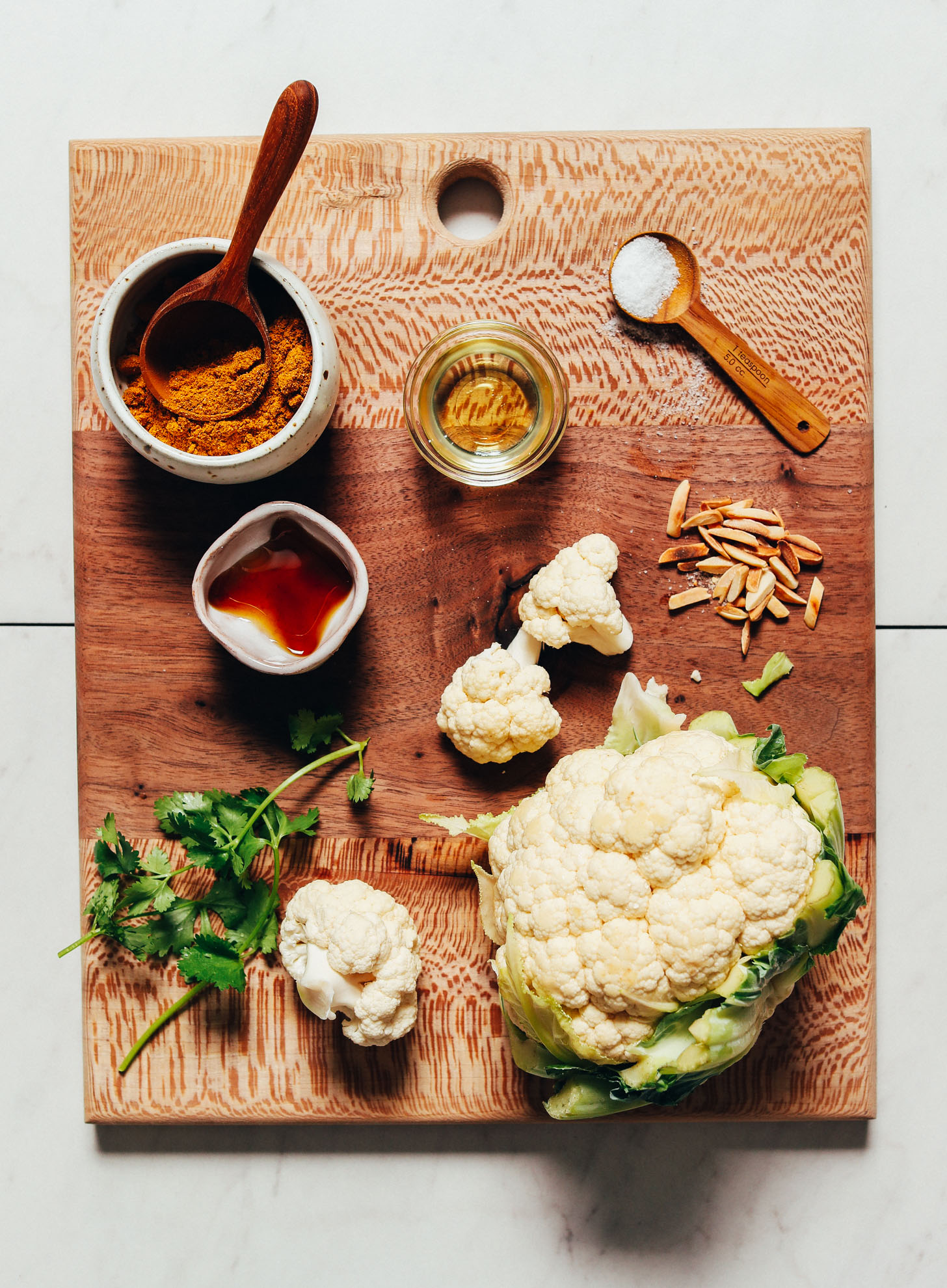 Wood cutting board with ingredients for making our Quick Crispy Cauliflower recipe