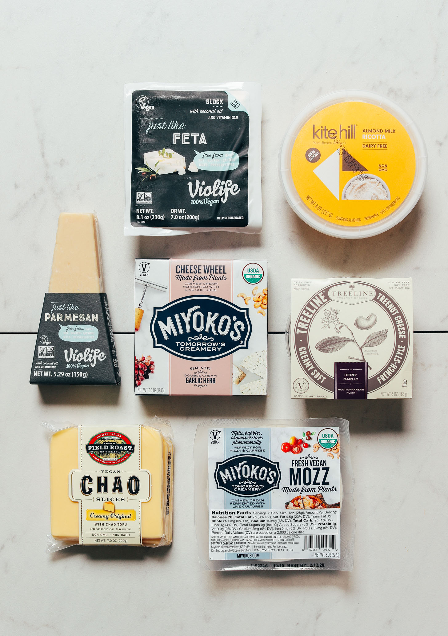 Top down shot of various brands of store-bought vegan cheeses for our unbiased review