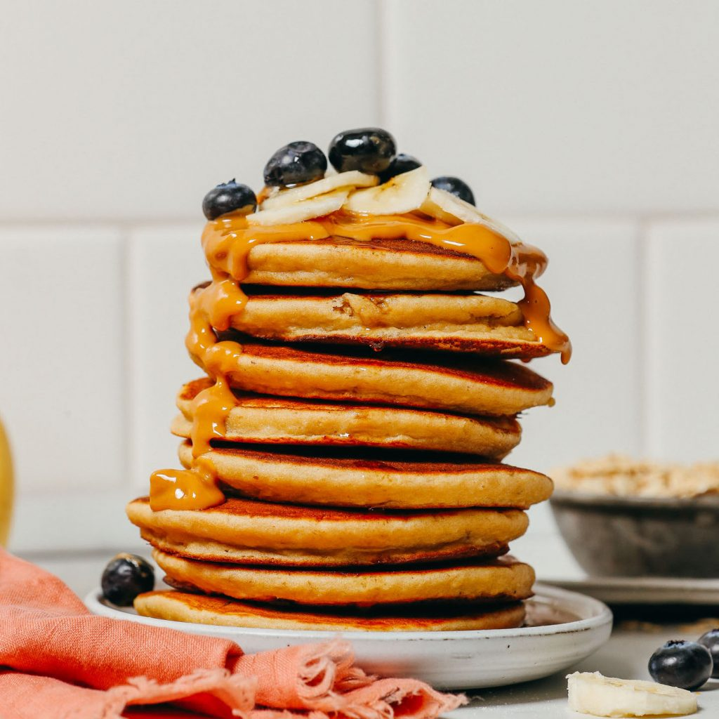 Stack of Blender Banana Pancakes topped with nut butter and fresh fruit