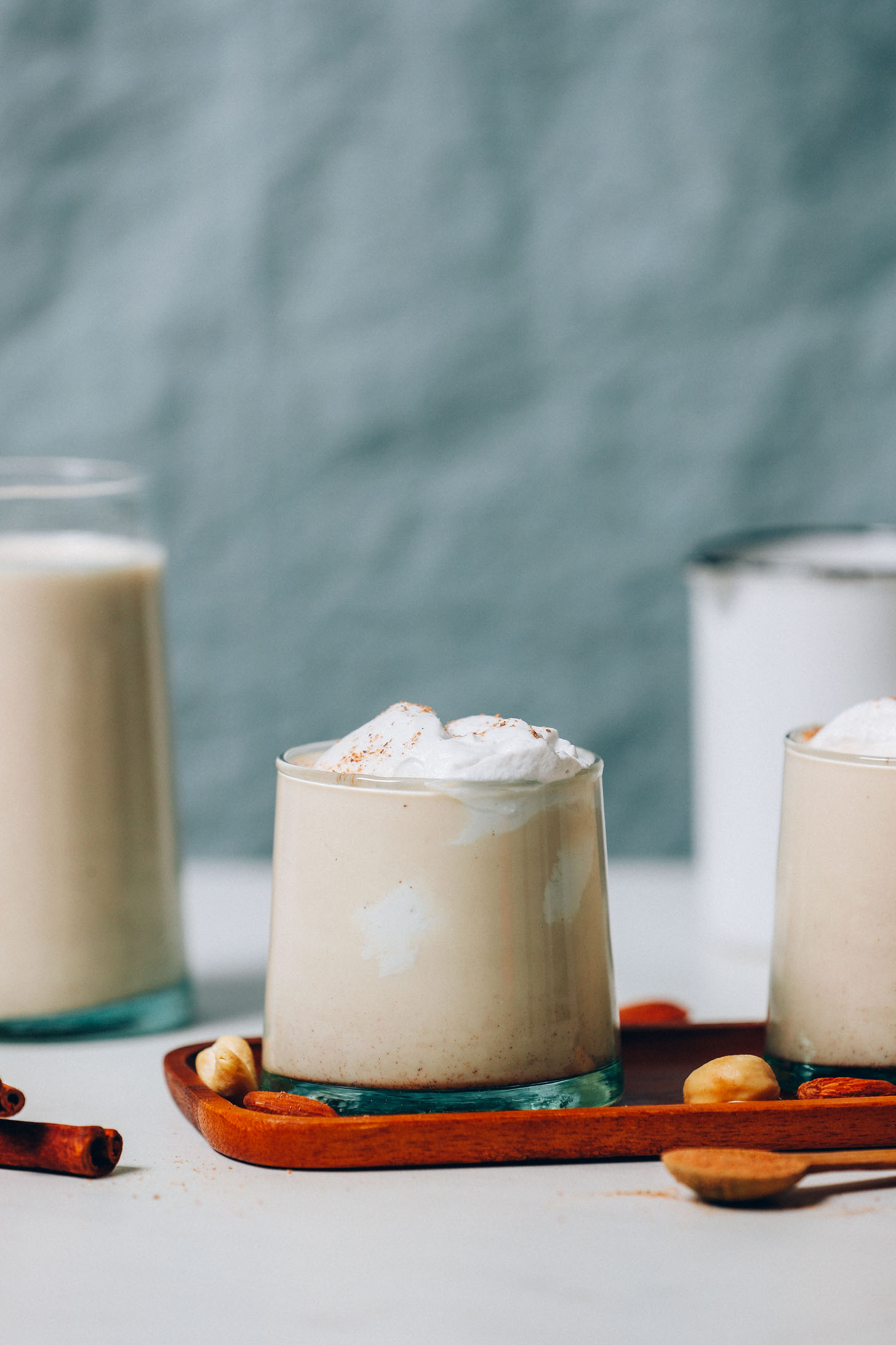 Two glasses of our Vegan Egg Nog recipe topped with coconut whipped cream