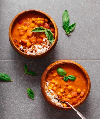 Two bowls of rice beside our Creamy Chickpea Tomato Peanut Stew recipe