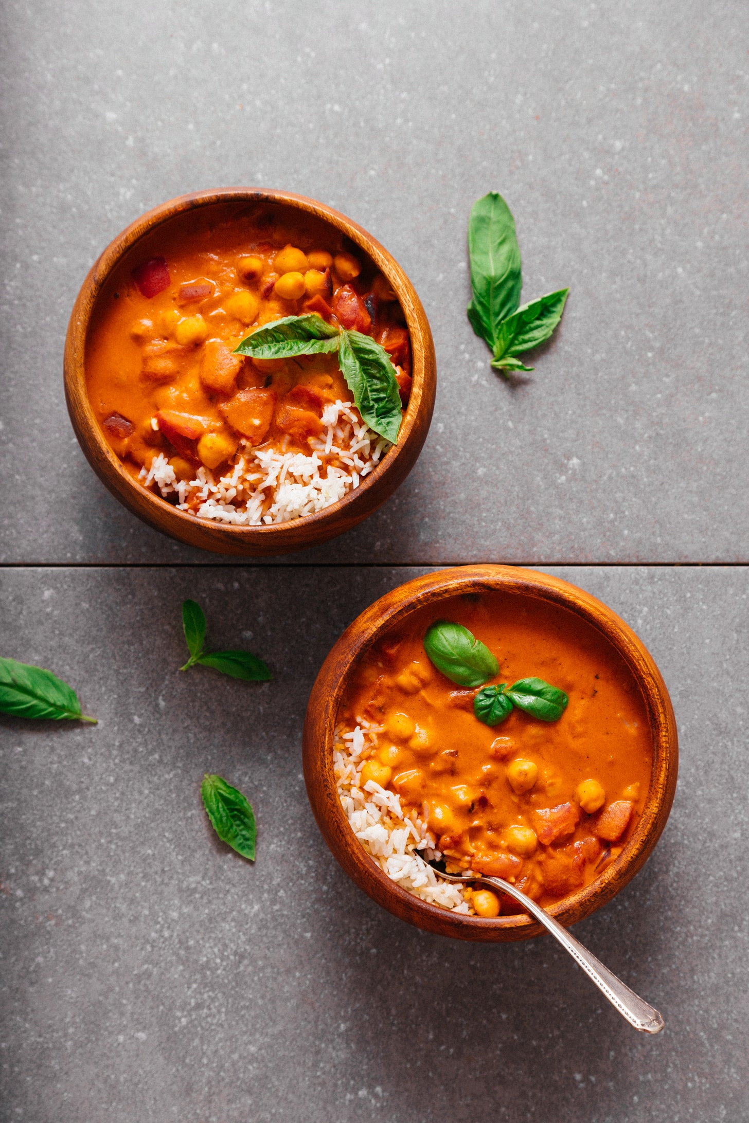 Two bowls of our 1-Pot Chickpea Tomato Peanut Stew recipe topped with fresh basil