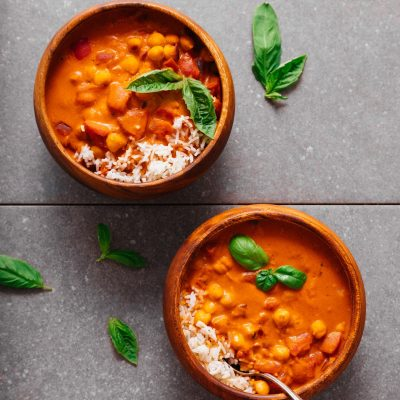 Bowls of Chickpea Tomato Peanut Stew served with rice and fresh basil
