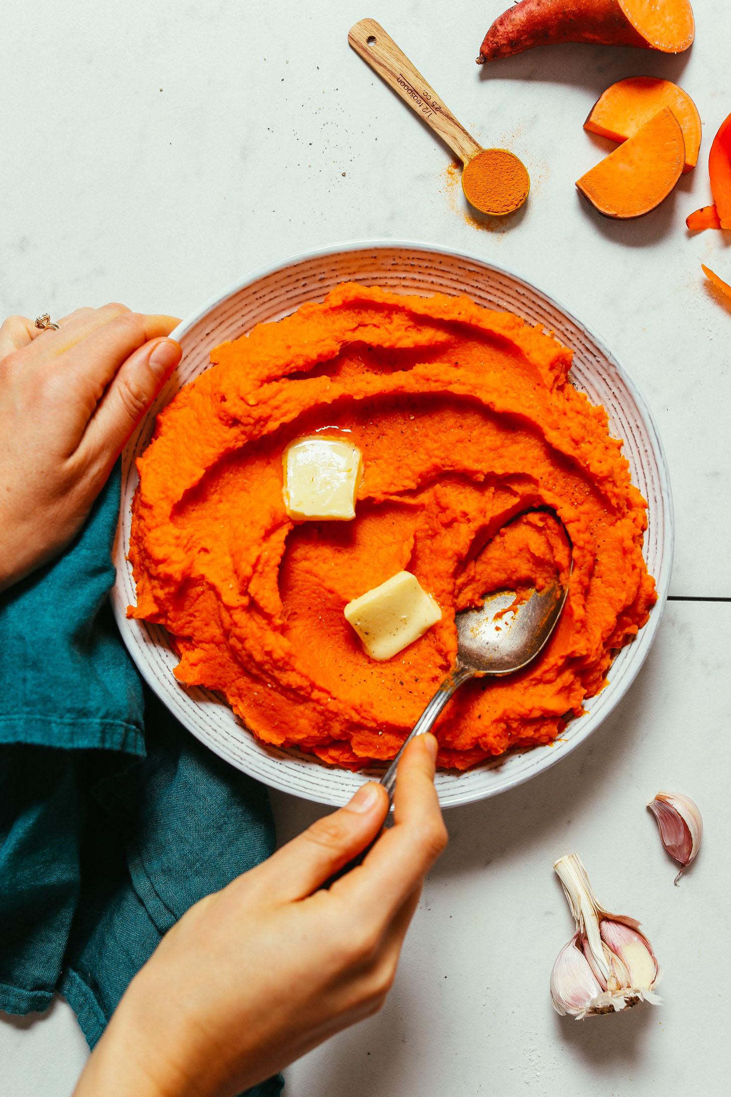 Tazón de puré de batatas saladas y zanahorias hechas con ajo y cúrcuma