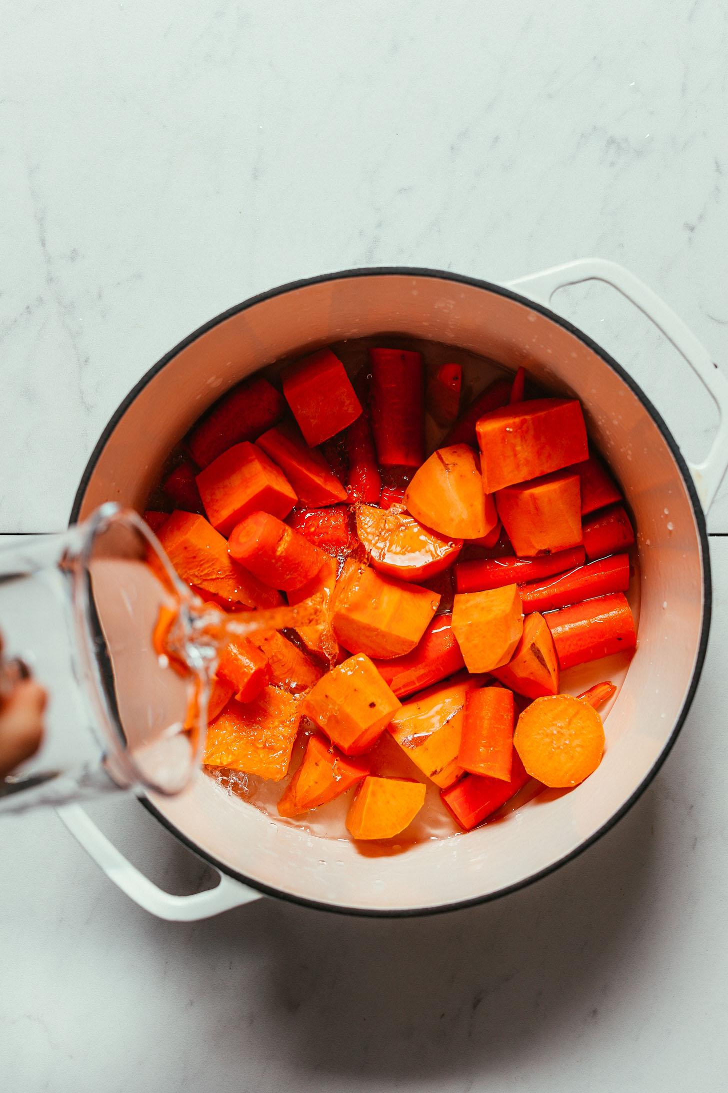 Verter agua sobre una sartén de zanahorias y batatas para hacer nuestra receta de puré de batatas