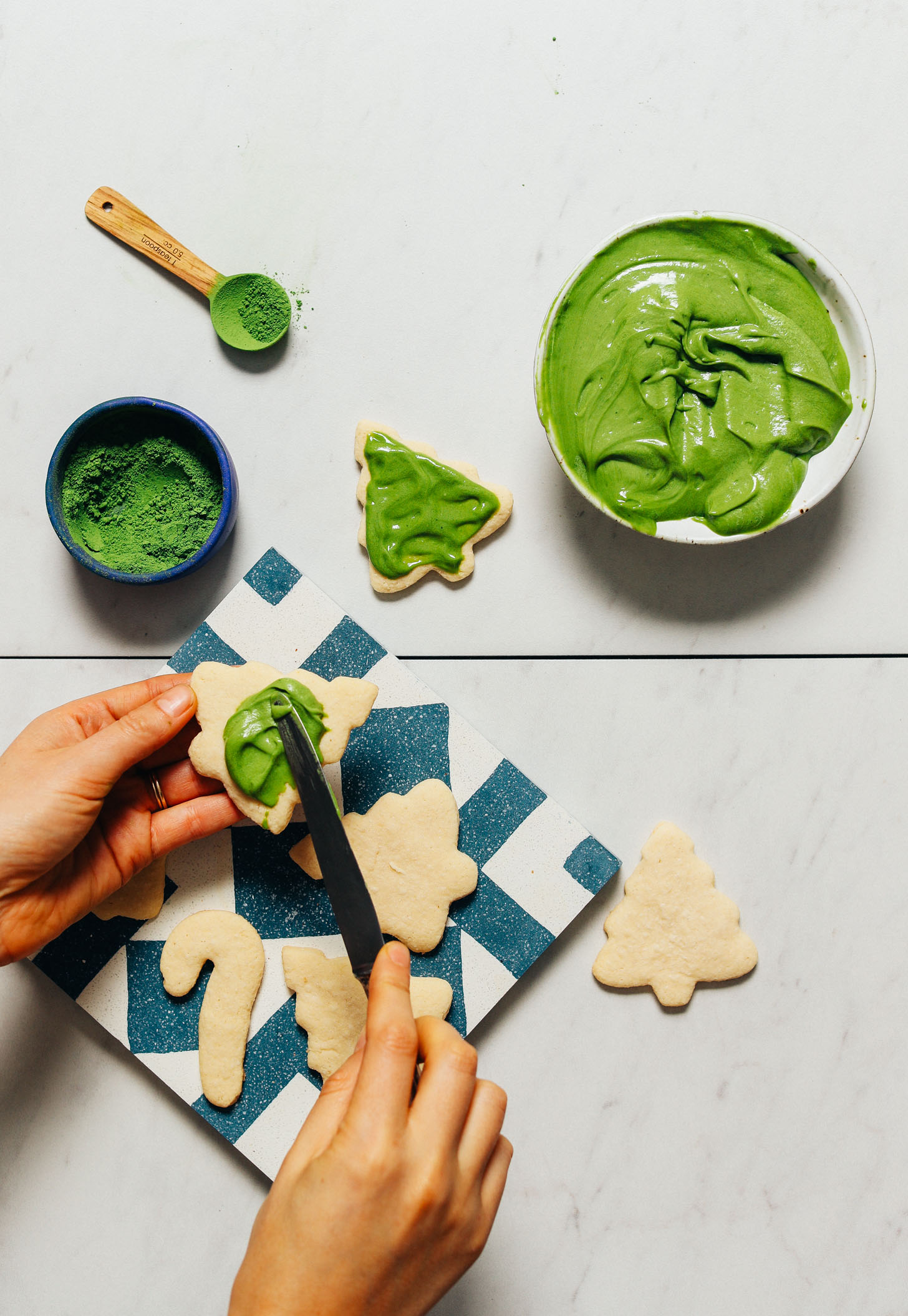 Spreading vegan frosting made with matcha onto a sugar cookie