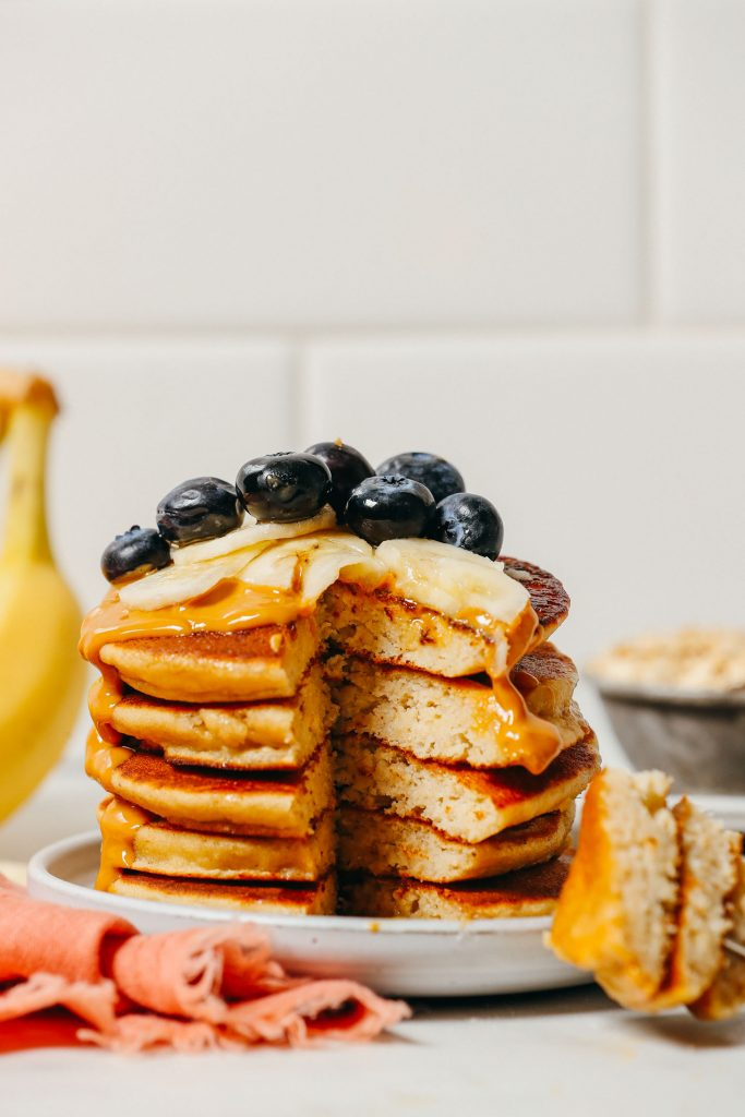 Sliced removed from a stack of Banana Pancakes topped with peanut butter and fresh fruit