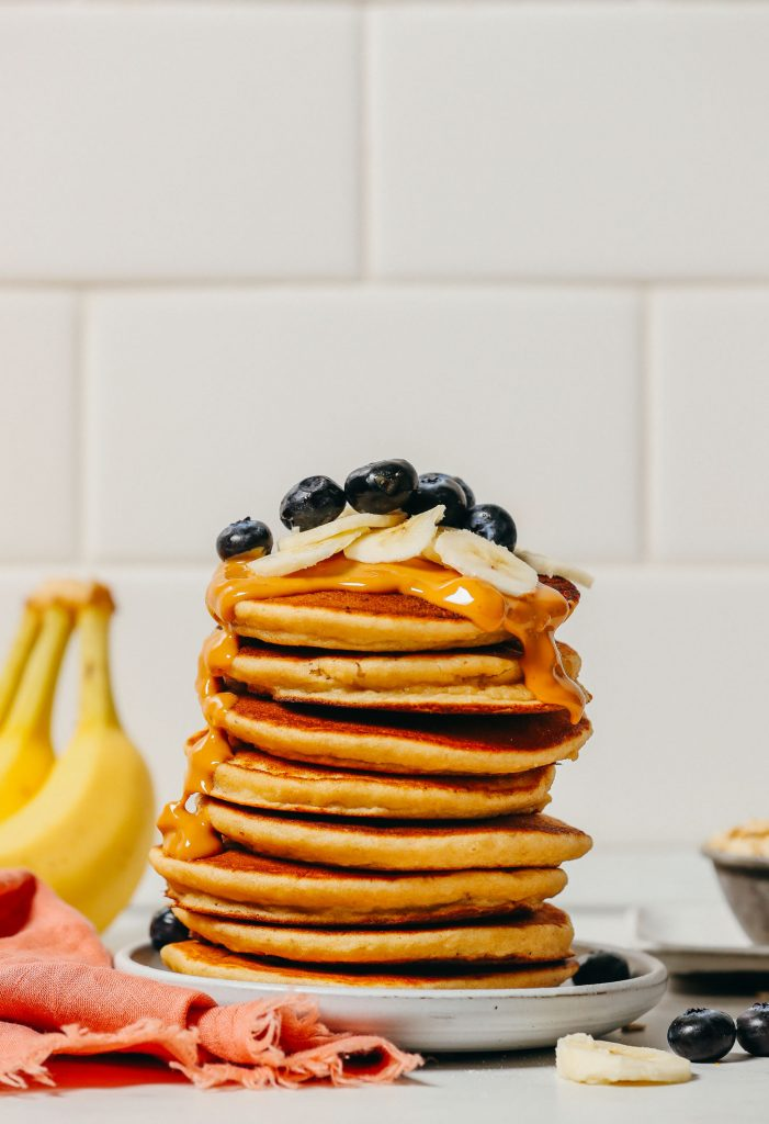 Stack of Blender Banana Pancakes topped with peanut butter and fresh fruit