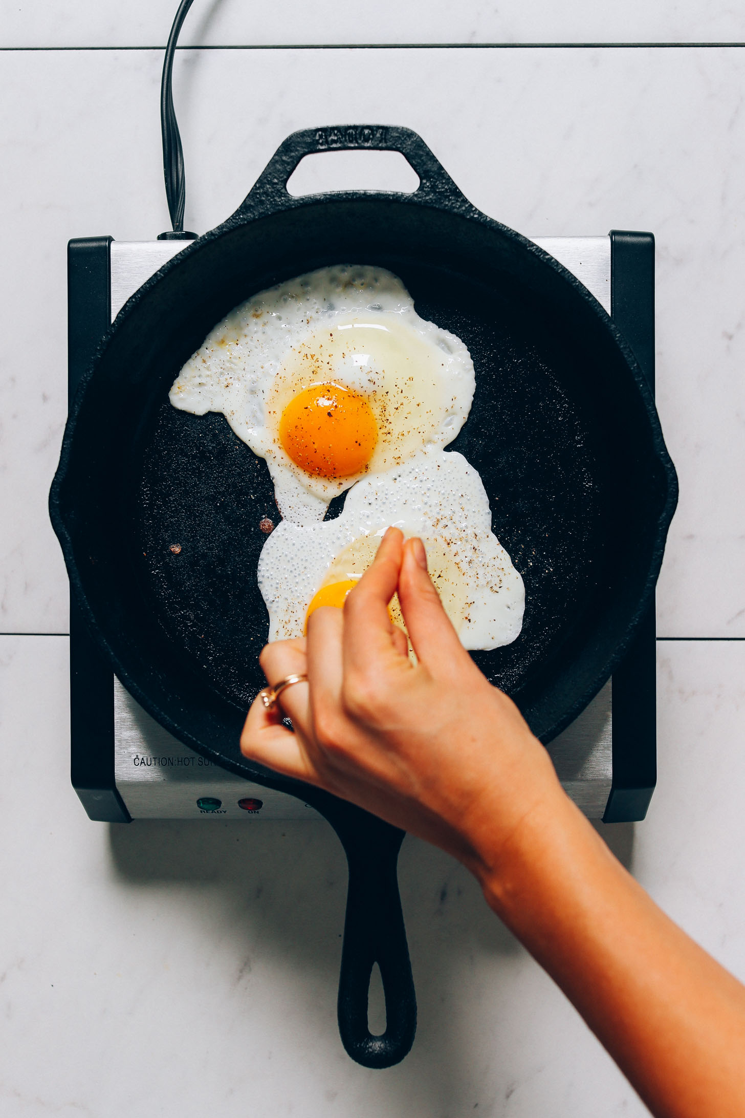Sprinkling black pepper onto fried eggs for our How to Cook an Egg recipe