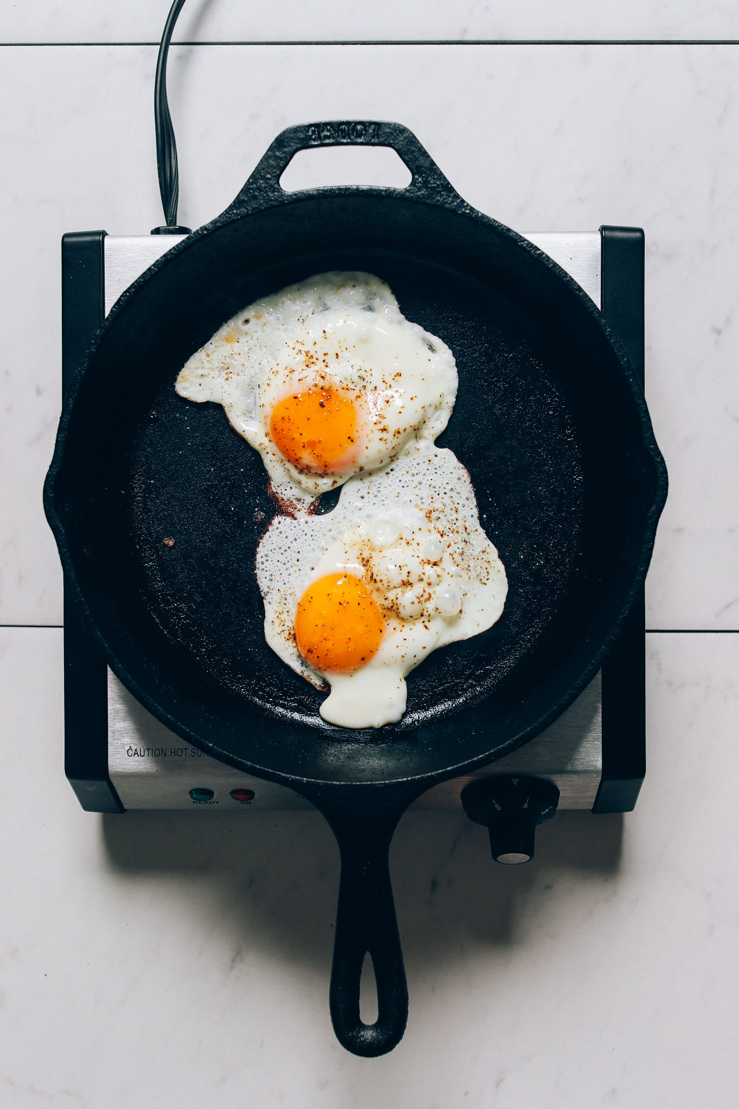 Skillet with two perfectly cooked sunny side up eggs