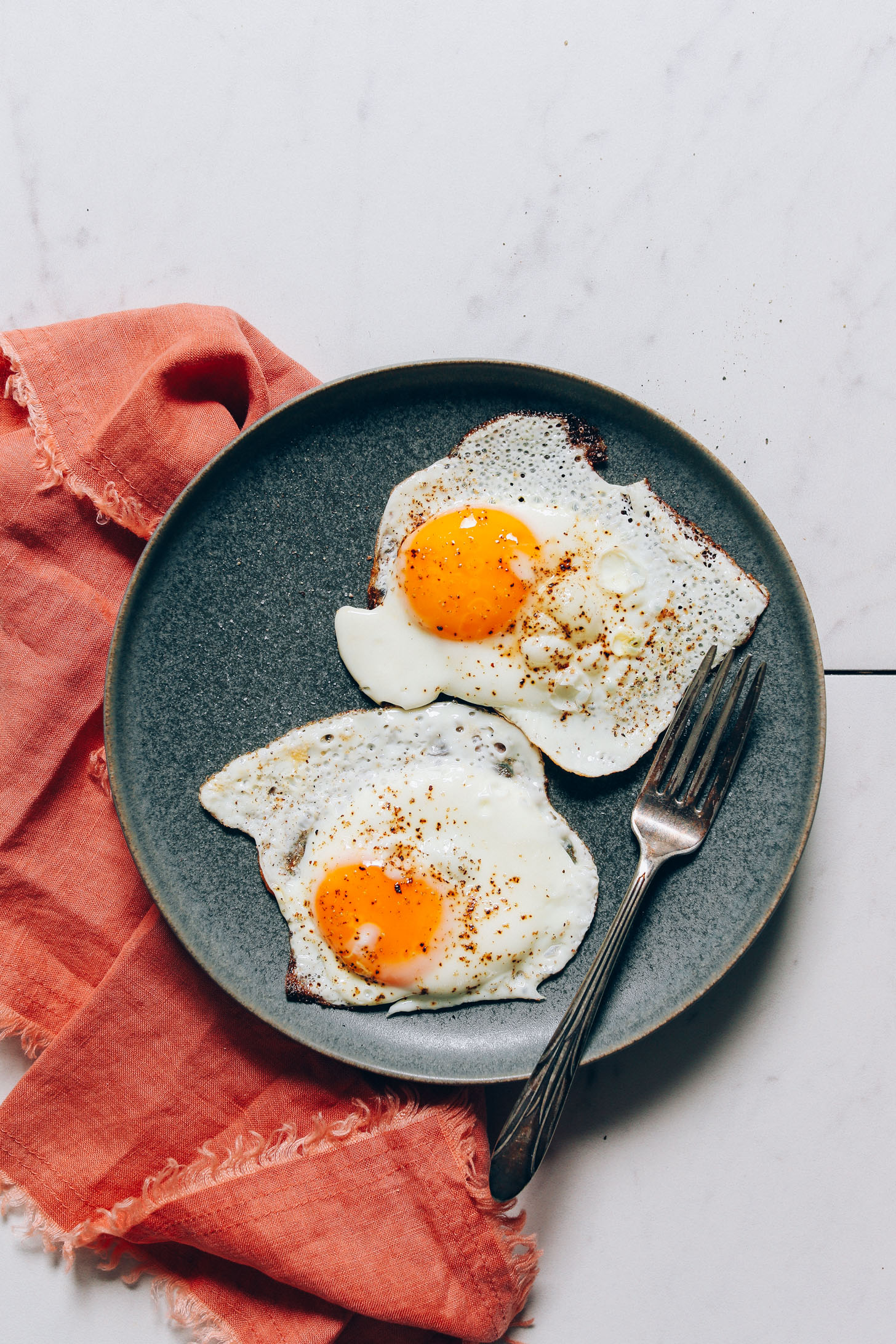 Plate of two perfectly cooked runny yolk eggs for our tutorial on How to Cook an Egg