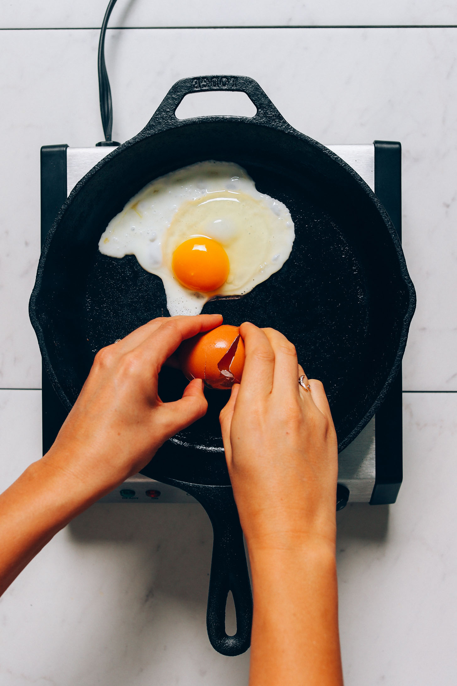 Cracking an egg in a skillet for our tutorial on How to Cook and Egg Perfectly Every Time