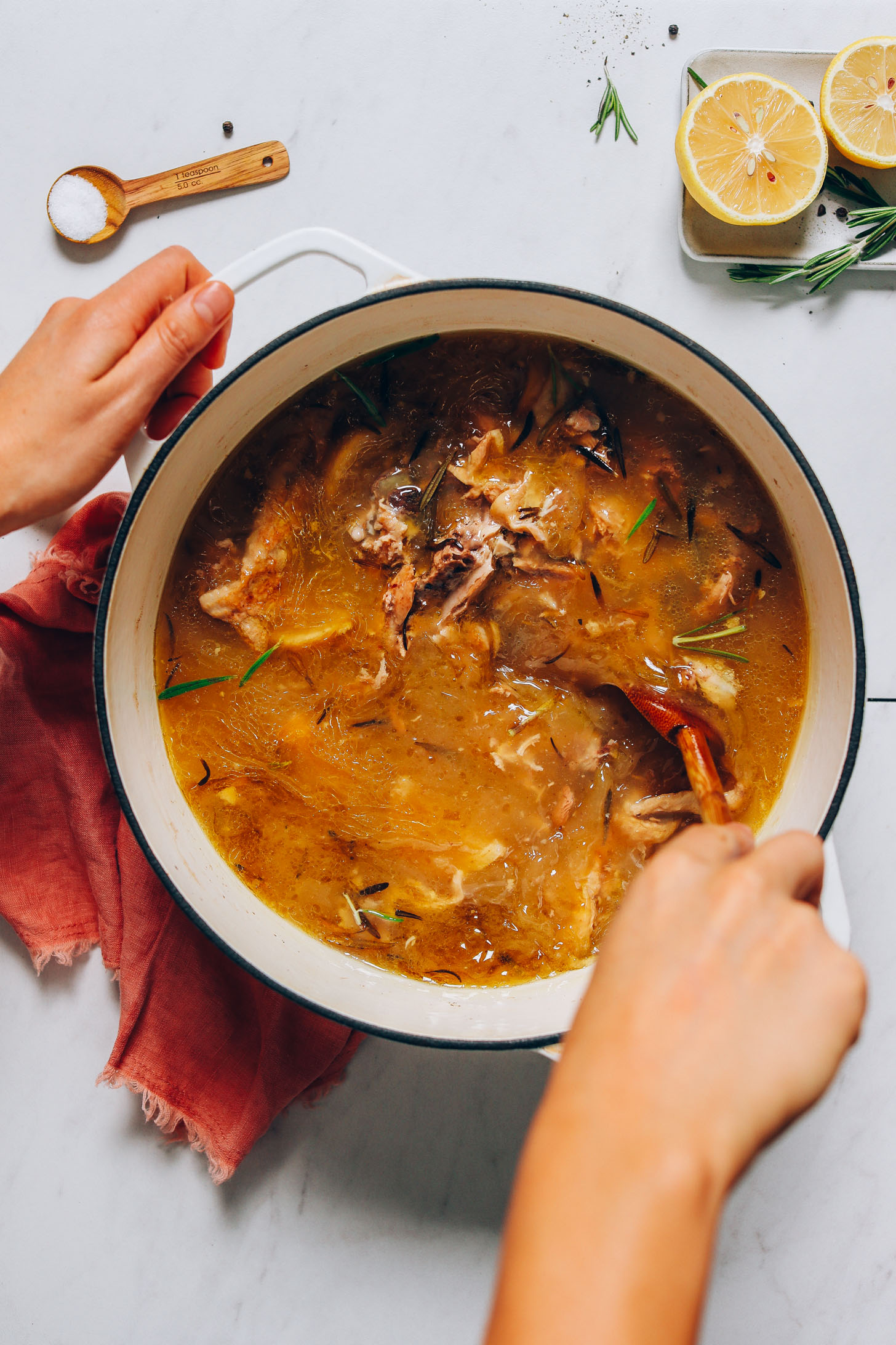 Using a wooden spoon to stir a pot of Homemade Bone Broth
