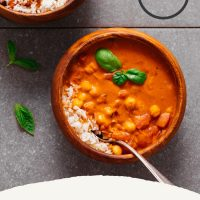 Bowls of Chickpea Tomato Peanut Stew with rice and topped with fresh basil