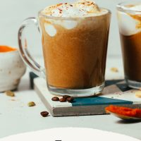 Mugs of our Easy Pumpkin Spice Latte recipe topped with coconut whipped cream and pumpkin pie spice