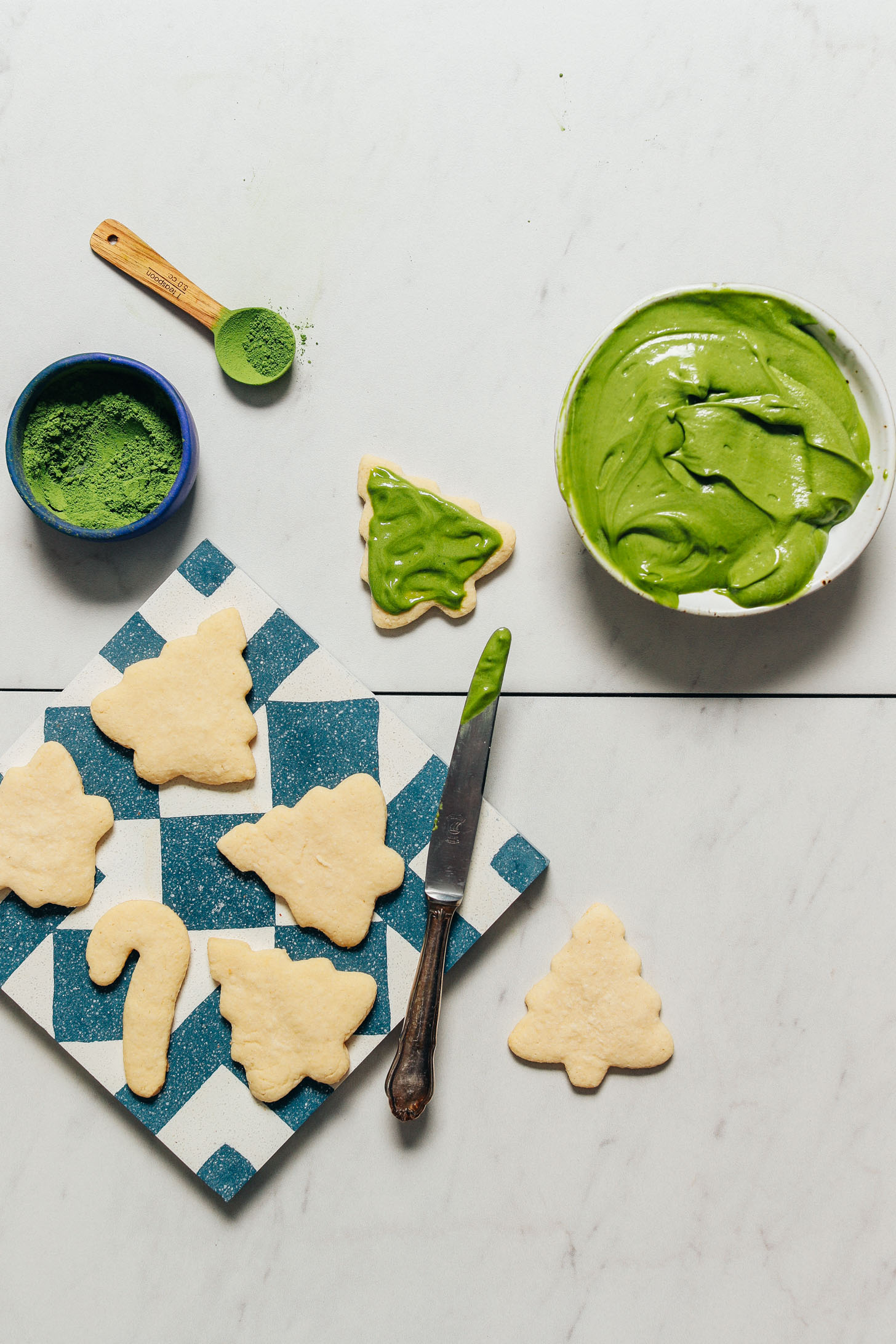 Bowl of matcha frosting beside Grain-Free Sugar Cookies for a natural Christmas cookie frosting idea