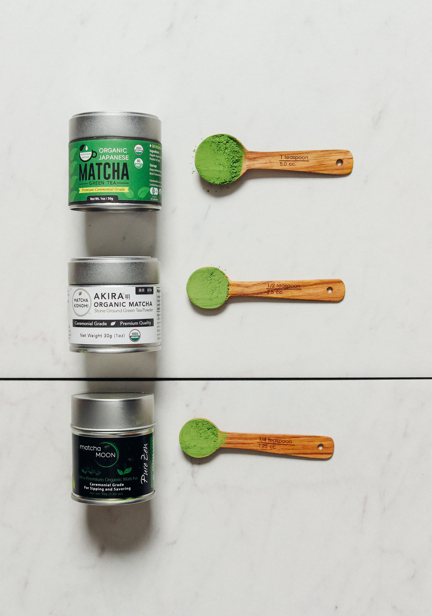 Spoonfuls of our top three favorite matcha brands beside their canisters